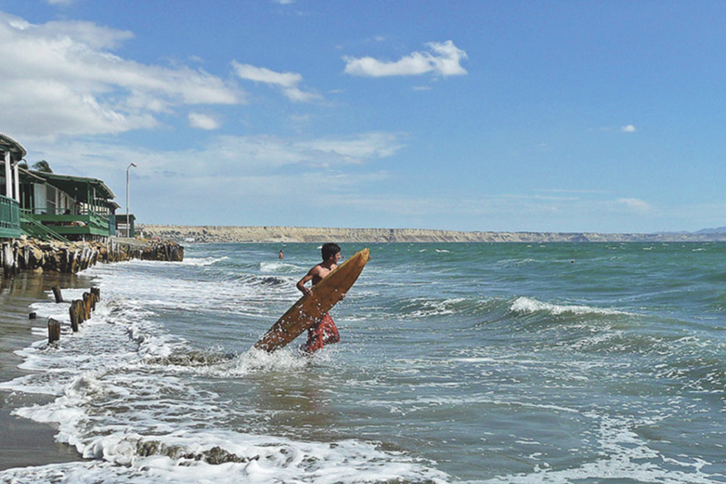 Surfista entrando al mar en la playa Colán.